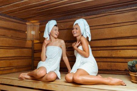 Photo pour Des amis souriants et séduisants dans des serviettes parlant au sauna - image libre de droit