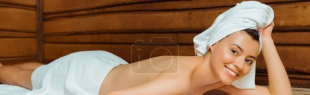 Photo for Panoramic shot of attractive and smiling woman in towels lying in sauna - Royalty Free Image