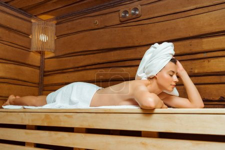 Photo pour Attractive woman in towels with closed eyes lying in sauna - image libre de droit