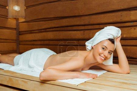 attraktive und lächelnde Frau in Handtüchern in der Sauna liegend