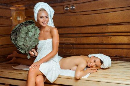 Photo pour Une jolie et souriante femme tenant un balai de bouleau et son amie couchée dans un sauna - image libre de droit
