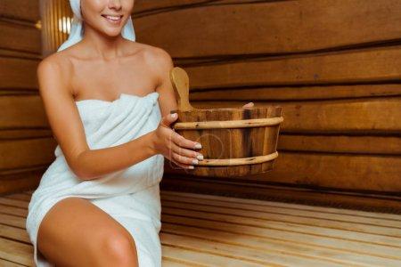 Photo pour Crochet vue d'une femme souriante dans une serviette tenant une baignoire en bois dans un sauna - image libre de droit
