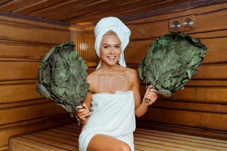 Photo pour Jolie femme souriante dans des serviettes tenant des balais de bouleau dans un sauna - image libre de droit