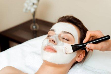 Photo pour Vue recadrée du cosmétologue appliquant masque facial sur la femme attrayante dans le spa - image libre de droit