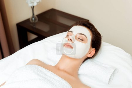 high angle view of attractive woman with mask on face lying on massage table in spa