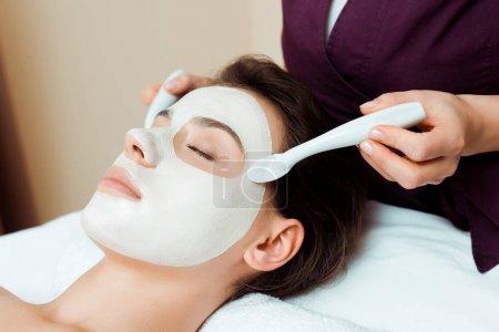Photo pour Croustillant vue d'un cosmétologue appliquant un masque facial sur une femme séduisante dans un spa - image libre de droit