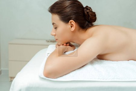 Photo pour Side view of attractive woman with closed eyes lying on massage table in spa - image libre de droit