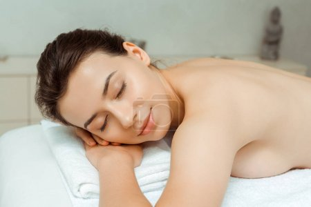 Photo for Attractive woman with closed eyes lying on massage table in spa - Royalty Free Image