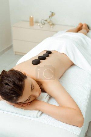 Photo pour Vue à grand angle d'une femme séduisante avec des pierres chaudes sur le dos allongée sur une table de massage - image libre de droit