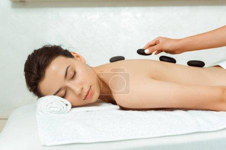 Photo pour Croc view of masseur doing hot stone massage to attractive woman in spa - image libre de droit