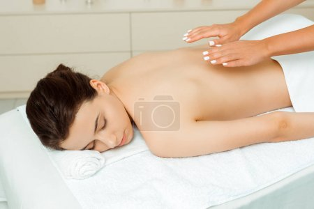Photo for Cropped view of masseur doing back massage to attractive woman in spa - Royalty Free Image