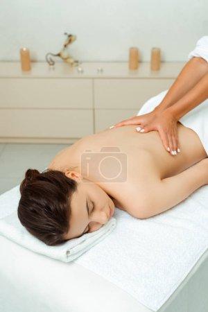 Photo pour Vue recadrée de masseur faisant le massage de dos à la femme attirante dans le spa - image libre de droit