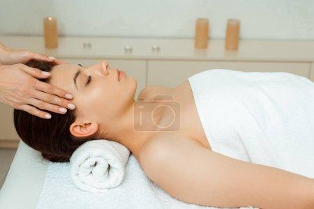 recortado vista de masajista haciendo masaje facial a atractiva mujer en spa