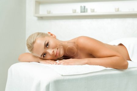 Photo pour Attractive and smiling woman looking at camera and lying on massage table in spa - image libre de droit
