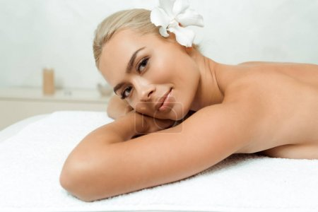 Photo pour Attractive and smiling woman with flower looking at camera and lying on massage table in spa - image libre de droit