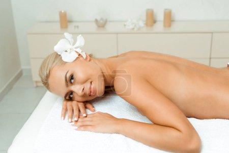 Photo pour Vue en hauteur d'une femme séduisante et souriante avec une fleur regardant la caméra et allongée sur une table de massage dans le spa - image libre de droit