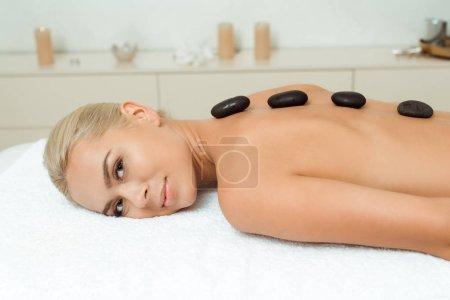 Photo pour Une femme souriante avec des pierres chaudes sur le dos allongée sur une table de massage au spa - image libre de droit