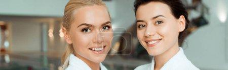 Photo pour Photo panoramique d'amis attirants et souriants en peignoir blanc regardant la caméra dans le spa - image libre de droit