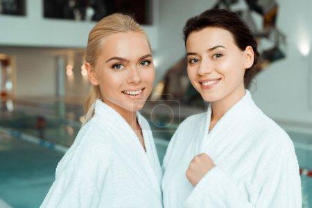 Photo pour Amis attrayants et souriants en peignoirs blancs regardant la caméra dans le spa - image libre de droit