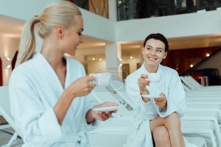 Photo pour Amis souriants en peignoirs blancs parlant et tenant des tasses dans le spa - image libre de droit