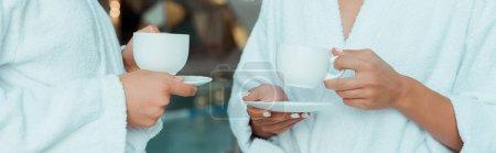 Photo pour Plan panoramique d'amis en peignoirs blancs tenant des tasses dans le spa - image libre de droit
