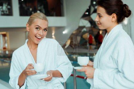 Photo pour Amis attrayants et souriants en peignoirs blancs tenant des tasses dans le spa - image libre de droit