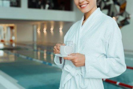 Photo pour Croustillant vue d'une femme souriante en peignoir blanc tenant une tasse de café dans un spa - image libre de droit