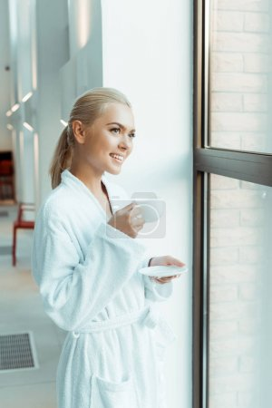 Photo for Attractive and smiling woman in white bathrobe holding cup of coffee and looking through window in spa - Royalty Free Image