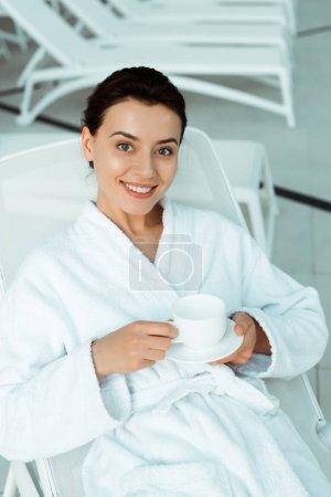 Photo pour Vue grand angle de femme attrayante et souriante en peignoir blanc tenant tasse de café dans le spa - image libre de droit