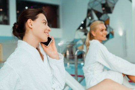 Photo pour Foyer sélectif de femme attrayante et souriante parlant sur smartphone et ami en arrière-plan dans le spa - image libre de droit
