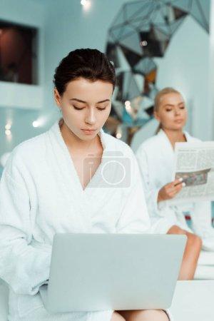 Photo pour Foyer sélectif de la femme attrayante en utilisant un ordinateur portable et un ami lecture journal sur fond dans le spa - image libre de droit