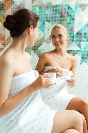 Photo pour Amis attirants et souriants dans des serviettes blanches parlant et tenant des tasses dans le spa - image libre de droit