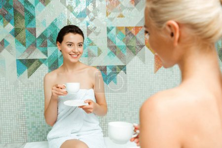 selective focus of attractive and smiling woman in white towel talking with friend and holding cup in spa