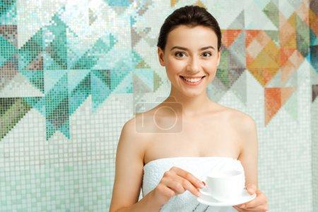 Photo pour Jolie femme souriante en serviette tenant une tasse de café au spa - image libre de droit