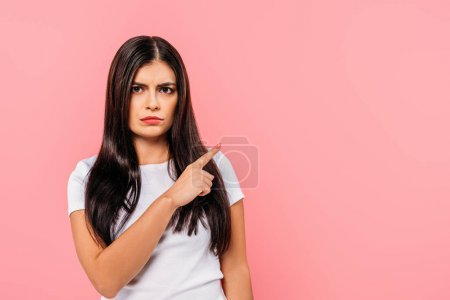 Photo for Sad pretty brunette girl pointing with finger at copy space isolated on pink - Royalty Free Image