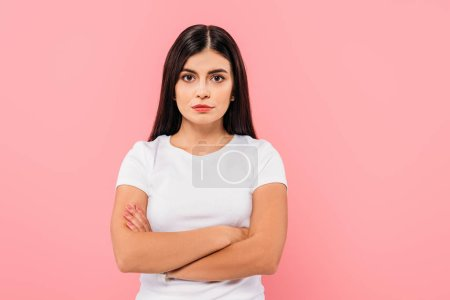 Photo for Serious pretty brunette girl with crossed arms isolated on pink - Royalty Free Image