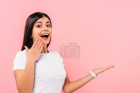 excited pretty brunette girl with open mouth pointing with hand at copy space isolated on pink