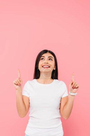 Photo pour Jolie brune jolie pointant les doigts vers le haut isolée sur rose - image libre de droit