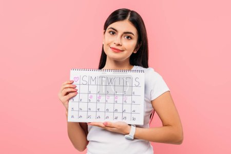 Photo pour Smiling pretty brunette girl holding period calendar isolated on pink - image libre de droit