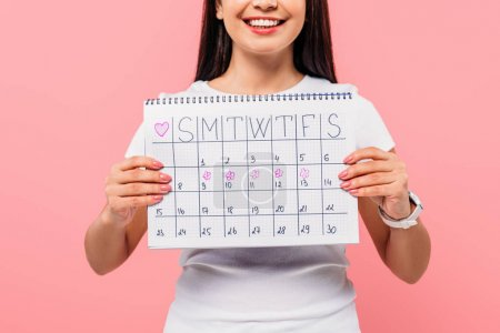Photo pour Cropped view of smiling girl holding period calendar isolated on pink - image libre de droit