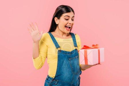 Photo pour Excité enceinte jolie fille tenant boîte cadeau isolé sur rose - image libre de droit