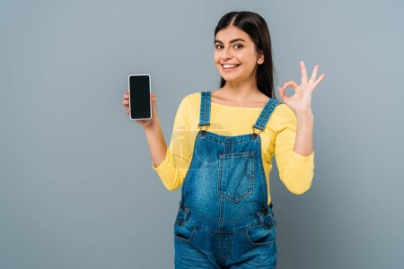 Photo pour Sourire enceinte jolie fille tenant smartphone avec écran blanc et montrant ok signe isolé sur gris - image libre de droit