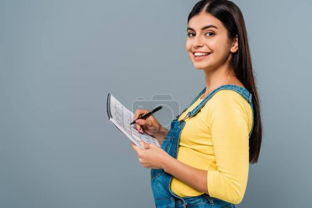 Photo pour Side view of smiling pregnant pretty girl holding period calendar and pen isolated on grey - image libre de droit