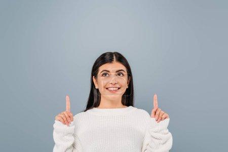 Photo pour Sourire jolie fille brune en pull blanc pointant les doigts vers le haut isolé sur gris - image libre de droit