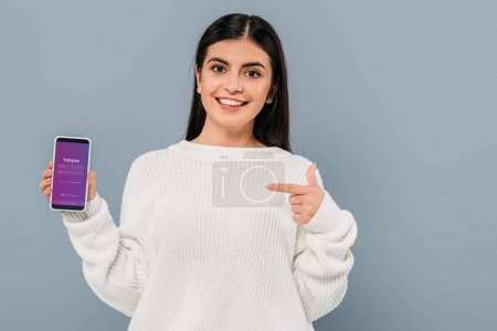 Photo for KYIV, UKRAINE - SEPTEMBER 20, 2019: smiling pretty brunette girl in white sweater pointing with finger at smartphone with instagram app isolated on grey - Royalty Free Image