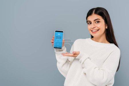 Photo pour KYIV, UKRAINE - 20 SEPTEMBRE 2019 : jolie fille brune souriante en pull blanc tenant smartphone avec application skype isolée sur gris - image libre de droit