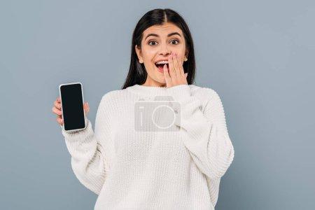 Photo pour Excitée jolie fille brune en pull blanc tenant smartphone avec écran vide isolé sur gris - image libre de droit