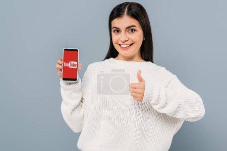 Photo pour Sourire jolie fille en pull blanc montrant smartphone avec application youtube et pouce vers le haut isolé sur gris - image libre de droit