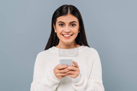 Photo pour Jolie brune souriante en chandail blanc utilisant un téléphone intelligent isolée sur gris - image libre de droit