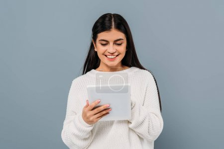 Photo for Smiling pretty brunette girl in white sweater using digital tablet isolated on grey - Royalty Free Image